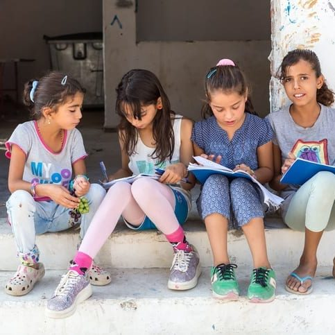 Lagadikia, Greece - August 25, 2016: Children sit on stairs in the refugee camp of Lagadikia, some 40km North of Thessaloniki, during the visit of UN high commissioner for refugees Filippo Grandi