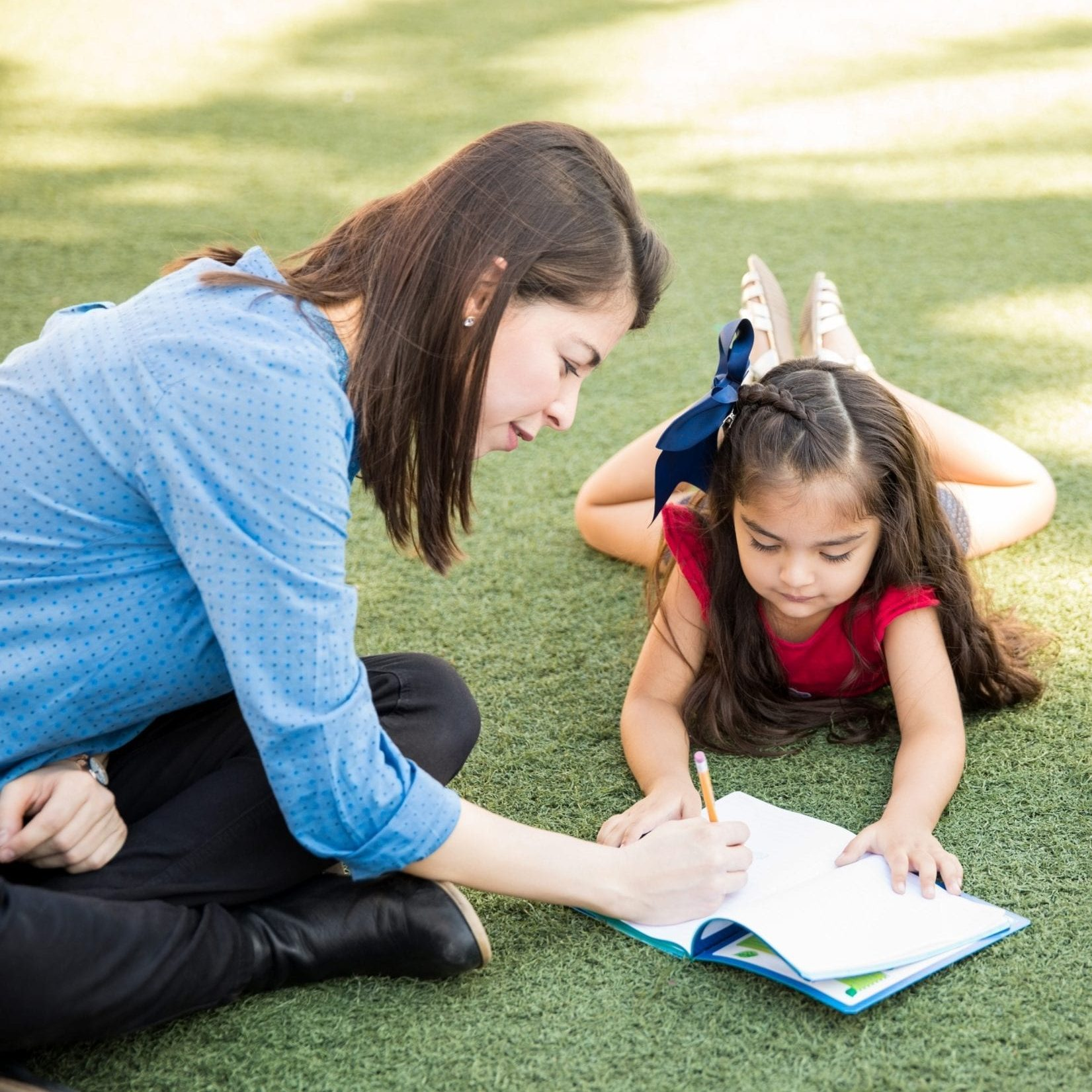 Patient female teacher helping her preschool student with a writing assigment while they take their class outdoors